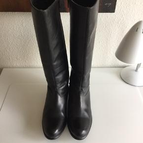 B&CO Støvler, Næsten som ny. Klostervænget - Flotte, lange sorte læderstøvler fra B&CO str. 38. Standen er NSN. De har elastikkile for bedre pasform i skaftet og lynlås. Nypris 900,- Mål: 42 cm lange, hælen er 3,5 cm., skaftet måler øverst på tværs 18 cm (halv størrelse af diameter - dertil kommer e