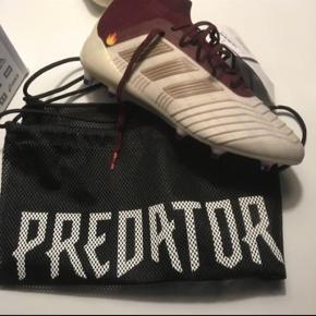 Adidas predator 18.1 FG W  Size 8 1/2 US  Aldrig brugt da det var for små. Der var et navn på siden af støvlen hvilket er blevet taget af og har skabt et lille mærke på siden af den ene støvle.  Ny pris: 1700kr