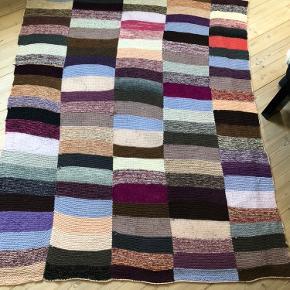 Håndstrikket uldplaid i lilla, rosa og brun. Måler 175cm x 150 cm. Kan maskinvaskes på uld/håndvaske program. Tørres fladt.