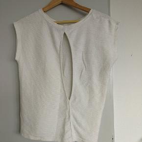 Chic, neutral bluse med åben ryg. Behagelig at have på og kan sættes sammen med meget forskelligt. Fejler intet. 100% bomuld.