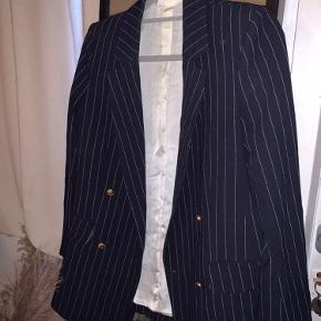 Sælger denne blazer fra H&M i mørkeblå med hvide striber og guld knapper.
