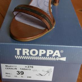 Brand: Troppa specielle Varetype: sandaler med lynlåse aldrig brugt Farve: Brun Oprindelig købspris: 1000 kr. Kvittering haves.  Har lidt svært ved at acceptere, at jeg nok aldrig kommer til at gå i disse fantastiske sandaler med de lækre lynlåsdetaljer.   De er købt for 1000 kr. Og jeg har ikke fået brugt dem endnu.  Troppa er et spansk mærke, som vist ikke føres i DK mere. Har aldrig set andre i disse sandaler (-:   Er vild med både farven, de lækre lynlås-detaljer og den pæne hæl. Har haft to andre fede par sko/sandaler i samme mærke). Men de her er bare en del lettere, tyndere og finere end de sko, jeg ellers går med.  Hvis du sidder derude og tænker, at dette er drømmeskoene - og at du vil få dem brugt - så slå til!   NB: Størrelsen er 39 selv om jeg selv ligger imellem 39 og 40 (39 mht længde, 40 mht bredde). Disse hér blev for store i str. 40, da de jo helst skal sidde til.  Sælger dem for kun 500 kr. plus porto (45 kr. sendt som forsikret TS-pakke uden omdeling med DAO, i den fine originalæske).  --- 0 ---  Se også de andre 10-15 lækre par sko, støvler og sandaler, jeg sælger (-: