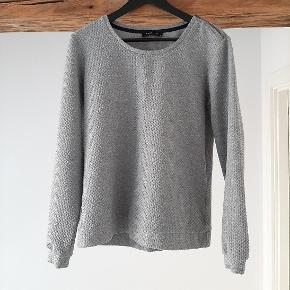 Grå trøje fra Modström.   Den er lidt lille i størrelsen; jeg bruger normalt størrelse M, og den passer mig fint.