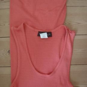 Lang top i 70%silke+30%bomuld, aldrig brugt. Brystvidde 70-106, længde 76. Farven er et sted mellem orange og laks.
