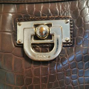 En læder taske fra DKNY med guld detaljer på som har mistet lidt sin farve. Str 22×25