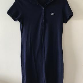 Lækker kjole fra Lacoste i det velkendte polostof som holder sig pænt selv efter en gang i vaskemaskinen. Kjolen er brugt et par enkelte gange og er perfekt både med bare ben eller et par nylonstrømper. Røgfrit hjem.
