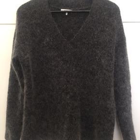 Fin sweater fra Ganni med V-udskæring. Aldrig brugt. Str. XS (stor i størrelsen). Bytter ikke. Kan sende med DAO, køber betaler fragt.