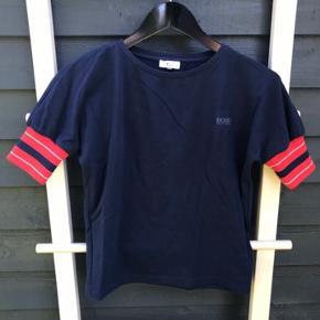 Mørkeblå kortærmet strikbluse fra Boss Hugo Boss, med røde, blå og hvid stribet rip forenden af ærmerne.  Den er brugt få gange og i fin stand.
