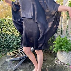 Smuk draperet kjole i en sort let skinnende fin polyester med rund halsudskæring med skinddetalje, halvlange store vidde ærmer og vidde omkring hofte og forneden. Kjolen har isyet underkjole og der er små indsyninger ved talje og bagpå. Lynlås i siden.  Materiale:100%Polyester