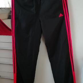 Adidas sports bukser i sort med neon orange striber, har elastik ved taljen og anklerne. Aldrig brugt. Prisen er ikke fast, så byd endelig! :)