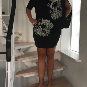 Virkelig fin top/kort kjole. Størrelsen hedder S/M. Den har et lille hul i det store ærme, det kan anes på fotoet i højre side bagerst. Det kan let syes uden at det ses, da ærmet er så stort. Købt for 1.499 kr.  Kan sendes med Dao for 38 kr.  eller afhentes i Århus C.