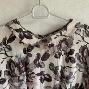 Super fin kjole fra Ganni med mange flotte detaljer. Fremstår rigtig fint. Grålige/rosa nuancer i blomsterne.