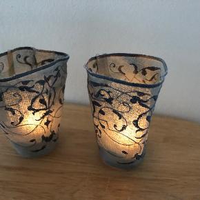 """To vidunderligt smukt designede lysestager til fyrfadslys fra berømmede bornholmske """"Baltic Sea Glass"""".  Skaber hygge i din hjem på de mørke aftener - og selv når de ikke er tændt vil de med deres varme design, smukke grønlige nuancer og ditto mønster pryde hjemmet.  En lysestage består af glasindsats til fyrfadslyset - og så en """"omsats"""" med glasbund og stof i varme grønne nuancer med mønster.  Højde: Ca 12 cm Diameter: Ca 8 cm  Nypris: 399 kr  Nyt/aldrig brugt. Leveres i flot sort originalindpakning fra Baltic See Glass (se billeder)  Måske også en god gaveidé? ..."""