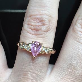 Sprit ny ring, guldbelagt med facetslebet smuk lyserød sten.   Ringen måler ca 1,75cm i indre diameter