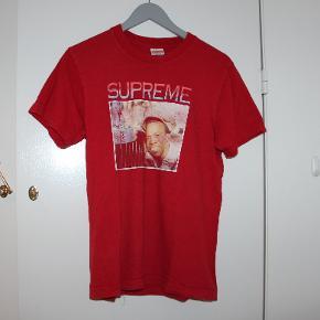 """Supreme """"Englishman"""" Tee  Cond 6 Lidt fade og cracking ved printet, som ses på 2. billede. Lille hul, som vist ved siden af en airpod på 3. billede. Intet og Str S (rare size)"""