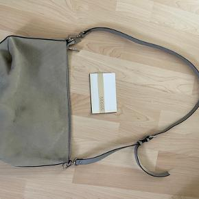 Grå ruskind decadent taske købt i 2015 mener jeg. Brugt meget sparsomt.  Måler 34 * 20 cm og rem kan vare 90-110 cm.  Har nogle pletter, er ikke forsøgt fjernet. Se billeder.