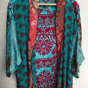 Smuk og farvestrålende silkejakke fra Sissel Edelbo (model Lotus), syet af sarier i fine mønstre. Farverne er især klar grøn og rød med lidt brunt i mønstret. Længden er 72 cm.