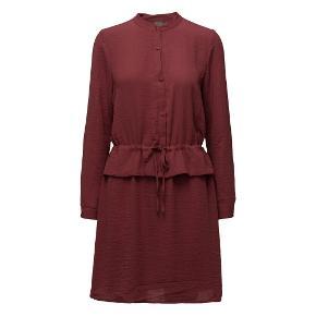 Bordeaux rød peplum kjole fra Ichi i str. M. Lidt stor af en medium, men kan snøres ind i livet og derfor tilpasses forskellige størrelser. Flæsekant i taljen og knaplukning fortil. Stof i 100% viskose. Kjolen fremstår helt ny og ubrugt - stadig med prisskilt (nypris 450 kr).   Sælges for minimum 150 kr plus porto
