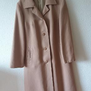 Skoen vintage frakke i klassiske snit. 100 % uld Den er camelsuld farvet, svaert at se pa billedet. Spoerg endelig