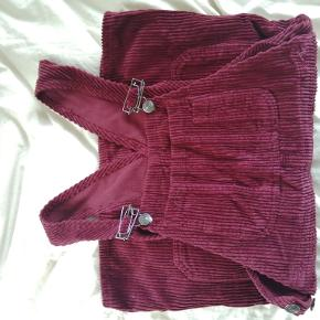 Skirt jumpsuit form Urban Outfitters in corduroy fabric. It has never been used, it is in perfect status and perfect for the winter :)