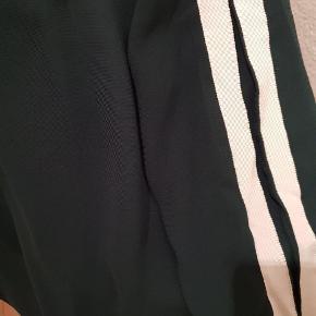 Mørkegrøn bluse med hvid detalje på ærmet, der giver det ellers elegante udtryk sporty twist.