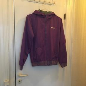 Fed lilla Björkvin jakke der er vind- og vandafskyende. Har lynlås foran, to lommer, hætte og ribkant nederst samt ved ærmerne.  Nypris: 799,-