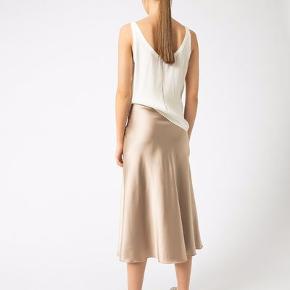 Ahlvar Galleri silke (93% silke og 7 % spandex)  nederdel i farven powder. Meget smuk og enkel nederdel, som kan styles både med sneakers og høje hæle. Aldrig brugt. Taljemål 78 cm, længde 80,5 cm.