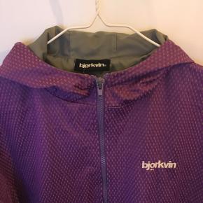 Fed lilla Björkvin sommer- overgangsjakke der er vind- og vandafskyende. Har lynlås foran, to lommer, hætte og ribkant nederst samt ved ærmerne. Ikke foret.  Nypris: 799,-