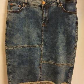 Sej, mørk blå denim nederdel, str. Zizzi-M = 46-48 med smarte slideffekter og rå underkant. Lommer for og bag. 98% bomuld og 2% elastan. Måler i taljen 96 cm, og længden er 62 cm. Aldrig brugt.