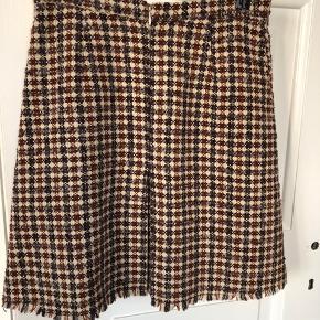 Smuk nederdel i tweet med lommer foran og lynlås bagved.