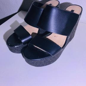 Sort sandal med høj kilehæl. 2 brede remme, kilehæl med jutebeklædning. Rigtig søde til en kjole eller jeans. Kilehæles højde: 10 cm Fremstår pæne men med små brugsspor (se billeder).