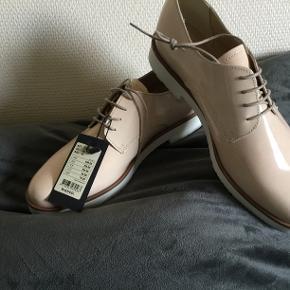 Helt nye sko, nude beige farve. Lædersko med lak shine. Helt almindelige i størrelsen. Kom med bud, nypris var 649,95