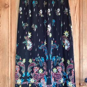 Fin foret nederdel med mønster og sølvtråde, lynlås og knap i siden.
