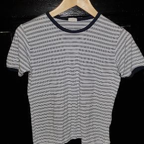 Inkluderer: Én løs t-shirt i let stof (den lysblå med mørkeblå og hvide striber) og to mavebluser i kraftigere stof med korte ærmer, hvoraf den ene er hvid- og sortternet og den anden er bordeaux, grå og rosa skotstern.