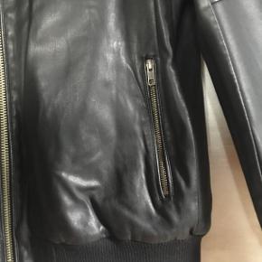 Harrington jakke i sort imiteret skind. Kraftige lynlåse til lukning foran, i lommerne og ved håndled. Dobbelt tryklås lukning i halsen. To skrålommer og en brystlomme foran + en inderlomme. Bred rib forneden. Pynte-syninger på oversiden af overarm. Helforet - to lag. Været i brug få timer - forkert størrelse. Oprindelig købspris 475,- Sender gerne på købers regning : DAO 44,-