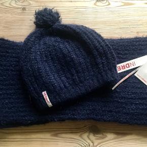 Fint Navy halstørklæde fra franske indress, der bl.a. Forhandles hos lubarol i Kbh. 36% alpaca , 40% polyacrilic , 14% wool og 10% polyamide. Har en helt fin glimmer tråd i strikken. Aldrig brugt og stadig med tags. Matchende hue sælges. Søgeord: mørkeblå halstørklæde tørklæde alpaca glitter uld glimmer navy strikket strik knit