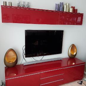 """Prisen er 1549 kroner og er ret fast.  Bestå Burs tv- og opbevarings møbler i rød højglans (fåes ikke længere).   Mål på tv skænk: L: 180cm D: 41cm H: 49cm  Mål på overskab(udvendige mål): L: 180cm D: 27cm H: 27,5cm  🌷Øverste del, indeholder 2 sideløbende rum til opbevaring. 🌷Nederste del indeholder 2 skuffer med tilhørende ekstra cd opbevaring(ialt 4 stk., se sidste billede) (eller hvad man ønsker de bruges til). Skufferne har hjul under hver. I midten er der 3 hylder (til fx. dvd, xbox el. lign.) med låger, så indholder ikke ses.  Jeg har sat standen som """"God, men brugt"""" - jeg har passet ret godt på det, så det har minimale brugsspor.  Nypris: ca. 3400 kroner.  ☝️ Indhold mv. medfølger (selvfølgelig) ikke 😉   🌸 SÅDAN HANDLER JEG 🌸  💙 BETALING VIA MOBILE PAY 💙 💚 Varen går til først betalende. 💛 Bytter/refunderer ikke/tager ikke varer retur. 🏠Hentes på Amager, tæt på Bella Center. 🚚Levering desværre ikke en mulighed, da vi ingen bil har.  VED AFHENTNING: Udlevering af vejnavn når du er på vej. Resten af adr. får du, når du er her. Bliver tit brændt af - på forhånd tak for forståelsen!🏡  Slået op flere steder."""