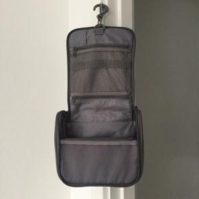 MUJI toilettaske, ideel til rejser, hvor den kan hænge på badeværelsesdøren. Har hele fem rum og små elastikker indeni til fx parfumer. Brugt få gange.