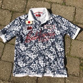 Rare Polo  T-shirt i str. 10 år  Super fed t-shirt med krave og stolpelukning. Rød svag skrift både for og bag. To flotte mærker på. Fin stand . Printet er med blomster og dødningehoveder.  #30dayssellout Pris: 50 kr pp