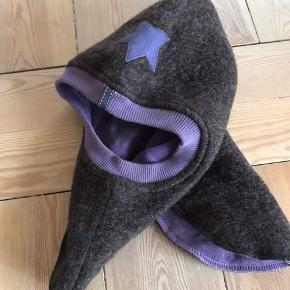 Den lækreste og varmeste hue fra Huttelihut i str 4-6 år. Den er i varm brun uld udvendig og blød lilla velour indvendig. Derudover en ribkant rundt ved hovedet, så den lukker tæt for vind og kulde. Den har en lilla stjerne i læder foran. Den har kun været på 1-2 gange og er som ny.