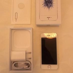 IPhone SE i hvid, 16 GB. Aldrig brugt. Oplader medfølger, høretelefonerne har jeg desværre haft i brug. BYD endelig.