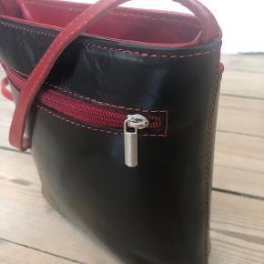 Italiensk håndlavet taske fra Vera Pelle i sort/rød.  Den er helt ny og har stadigvæk plastik indvendig. Jeg får den ikke brugt, og derfor sælges den.  Jeg har fået den i gave, så kvitteringen har jeg ikke.  Remmen er 135cm, og justerbar.