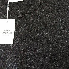 Smukkeste bluse i metallic look. Har lillet ærme og v-udskæring. Style Kassey.  Farven hedder metallic glam og er sort med forskellige andre farver .  Mål: længde 60 cm bryst 2 x 50 cm  NYpris kr 900 - sælges for kr 350 p.p.  Sælger masser andet tøj og sko fra bl.a.: Acne, Rabens saloner, Day, Custommade,