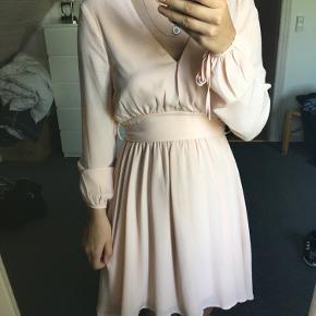 Rigtig fin beige/fersken farvet kjole. Brugt én gang, så næsten som ny. Er blevet syet ved brystet, da den var lidt for nedringet.