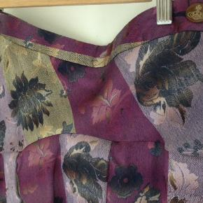 str. 40, Vivienne Westwood  smuk draperet nederdel med livvidde 76 cm. Str. mrk. 46.  Anvendt én gang.  Længde højre side: 59 cm Længde venstre side: 72 cm  Yderstof: 70 % acetate / 21 % viscose / 9 % uld Foer: 100 % viscose