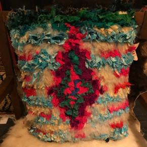 Amlou specialdesignet boucherouite pude. Måler 40x40 cm. Der medfølger ecocertificeret inderpude. Puden er håndlavet i Marokko og fremstillet af genbrugsstoffer