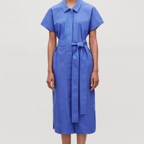 Super smuk kjole fra COS med bindebælte i taljen i 100% bomuld, foran i en vævet kvalitet og bagpå i super blød jersey. Str M ny med prisskilt.