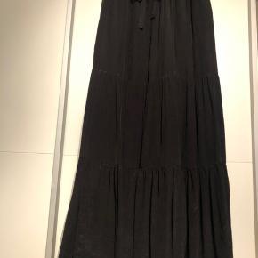 Fin let nederdel i to lag med bindebånd og lommer.