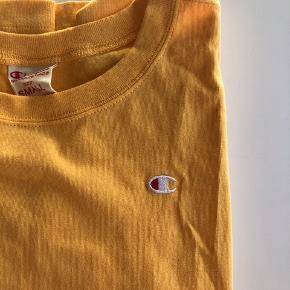 Champion t-shirt i størrelse small. Fejlkøb - kun brugt en enkelt gang, da farven desværre ikke er mig, og den har derfor bare ligget i mit skab til nu. Mangler, som det fremgår af billedet - en omgang med strygemaskinen, men ellers er den helt som ny.