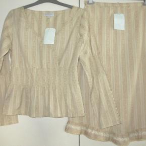 100 % NYT sæt, stadig med tag: Bluse og nederdel, som kan bruges hver for sig eller sammen. Stoffet, som er sandfarvet. er med indvævede striber. Materialet er 100 % cotton.  Blusen er str M og med elastik i livet. Brystvidde: 49 cm x 2 Længde: 59 cm  Nederdelen er str S. Den er asymetrisk forneden, og den har elastik bag i linningen. Livvidde: 34-36 cm x 2 (pga elastik) Længde: 70-75 cm   Ingen byt og prisen er fast